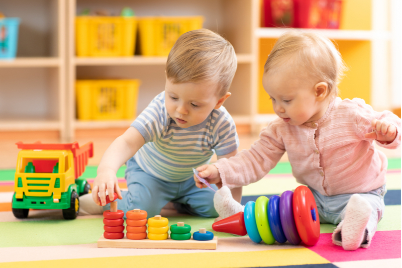 two babies playing in childcare nursery