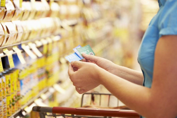 woman with food coupons in supermarket to save money